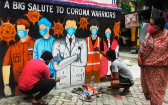 Artists give finishing touches to a mural depicting frontline workers during a day-long complete lockdown imposed by the state government against the surge in COVID-19 coronavirus cases in Kolkata on August 5, 2020. (Photo by Dibyangshu SARKAR / AFP) (Photo by DIBYANGSHU SARKAR/AFP via Getty Images)