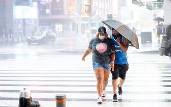 NEW YORK, NEW YORK - AUGUST 04: People wearing masks walk with an umbrella during heavy rain and wind in Times Square as Tropical Storm Isaias makes landfall during Phase 4 on August 04, 2020 in New York City. The fourth phase allows outdoor arts and entertainment, sporting events without fans and media production. (Photo by Alexi Rosenfeld/Getty Images)