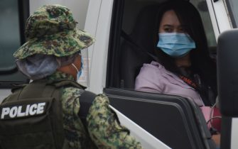 "A police officer (L) speaks to a motorist at a checkpoint as they conduct identity checks during a new round of lockdown measures for the COVID-19 coronavirus outbreak, along a road in Manila on August 4, 2020. - Millions of people in the Philippines went back into lockdown on August 4 as global coronavirus infections keep soaring, with the World Health Organisation warning against relying on a vaccine ""silver bullet"" to end the pandemic. (Photo by Ted ALJIBE / AFP) (Photo by TED ALJIBE/AFP via Getty Images)"