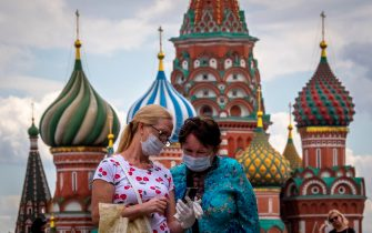 Two women wearing face masks to protect against the coronavirus disease look at a screen of a smartphone in front of St. Basil's Cathedral in downtown Moscow on July 30, 2020. (Photo by Yuri KADOBNOV / AFP) (Photo by YURI KADOBNOV/AFP via Getty Images)