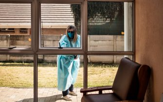 The relative of a resident at Casa Serena, an Old Age home in Johannesburg, looks through a window to check on her loved one on July 22, 2020. - Senior residents of the old age home Casa Serena in Johannesburg are devastated by a rigid COVID-19 coronavirus quarantine, following a deadly spike in cases inside the institution. At least 17 facilities were affected by COVID-19 coronavirus in the Gauteng province. (Photo by MARCO LONGARI / AFP) (Photo by MARCO LONGARI/AFP via Getty Images)