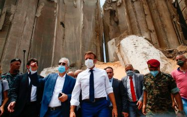 French President Emmanuel Macron (C), surrounded by Lebanese servicemen, visits the devastated site of the explosion at the port of Beirut, on August 6, 2020 two days after a massive explosion devastated the Lebanese capital in a disaster that has sparked grief and fury. - French President Emmanuel Macron visited shell-shocked Beirut on August 6, pledging support and urging change after a massive explosion devastated the Lebanese capital in a disaster that left 300,000 people homeless. (Photo by Thibault Camus / POOL / AFP) (Photo by THIBAULT CAMUS/POOL/AFP via Getty Images)