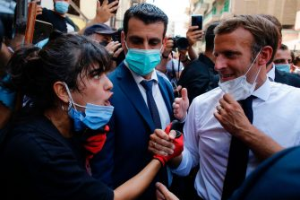 French President Emmanuel Macron listens to a resident as he visits a devastated street of Beirut, Lebanon, on August 6, 2020 a day after a massive explosion devastated the Lebanese capital in a disaster that has sparked grief and fury. - French President Emmanuel Macron visited shell-shocked Beirut Thursday, pledging support and urging change after a massive explosion devastated the Lebanese capital in a disaster that has sparked grief and fury. (Photo by Thibault Camus / POOL / AFP) (Photo by THIBAULT CAMUS/POOL/AFP via Getty Images)