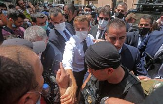 TOPSHOT - French President Emmanuel Macron greets people as he visits the Gemmayzeh neighborhood which has suffered extensive damage due to a massive explosion in the Lebanese capital, on August, 6. 2020. - French President Emmanuel Macron visited shell-shocked Beirut, pledging support and urging change after a massive explosion devastated the Lebanese capital in a disaster that has sparked grief and fury. (Photo by - / AFP) (Photo by -/AFP via Getty Images)