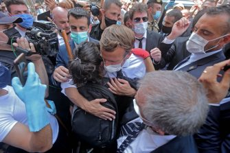 TOPSHOT - A Lebanese youth hugs French President Emmanuel Macron during a visit to the Gemmayzeh neighborhood, which has suffered extensive damage due to a massive explosion in the Lebanese capital, on August 6, 2020. - French President Emmanuel Macron visited shell-shocked Beirut, pledging support and urging change after a massive explosion devastated the Lebanese capital in a disaster that has sparked grief and fury. (Photo by - / AFP) (Photo by -/AFP via Getty Images)