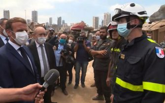 A video grab shows French President Emmmanuel Macron (L) speaking with a member of a French rescue team which arrived overnight to support relief efforts at the port of Lebanon's capital Beirut, on August 6, 2020, where a massive explosion killed more than 100 people and devastated the city. (Photo by - / POOL / AFP) (Photo by -/POOL/AFP via Getty Images)