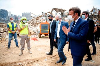 French President Emmanuel Macron (R) salutes as he arrives to visit the devastated site of the explosion at the port of Beirut, on August 6, 2020 two days after a massive explosion devastated the Lebanese capital in a disaster that has sparked grief and fury. - French President Emmanuel Macron visited shell-shocked Beirut on August 6, pledging support and urging change after a massive explosion devastated the Lebanese capital in a disaster that left 300,000 people homeless. (Photo by Thibault Camus / POOL / AFP) (Photo by THIBAULT CAMUS/POOL/AFP via Getty Images)