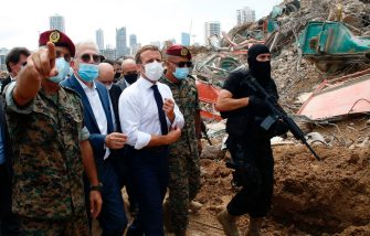 TOPSHOT - French President Emmanuel Macron (C), surrounded by Lebanese servicemen, visits the devastated site of the explosion at the port of Beirut, on August 6, 2020 two days after a massive explosion devastated the Lebanese capital in a disaster that has sparked grief and fury. - French President Emmanuel Macron visited shell-shocked Beirut on August 6, pledging support and urging change after a massive explosion devastated the Lebanese capital in a disaster that left 300,000 people homeless. (Photo by Thibault Camus / POOL / AFP) (Photo by THIBAULT CAMUS/POOL/AFP via Getty Images)