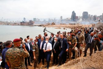 TOPSHOT - French President Emmanuel Macron (C), flanked by French Foreign Affairs Minister Jean-Yves Le Drian (C,R) visits the devastated site of the explosion at the port of Beirut, on August 6, 2020 two days after a massive explosion devastated the Lebanese capital in a disaster that has sparked grief and fury. - French President Emmanuel Macron visited shell-shocked Beirut on August 6, pledging support and urging change after a massive explosion devastated the Lebanese capital in a disaster that left 300,000 people homeless. (Photo by Thibault Camus / POOL / AFP) (Photo by THIBAULT CAMUS/POOL/AFP via Getty Images)