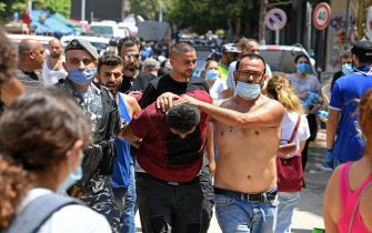 A Lebanese policeman and a citizen detain a thief, who was trying to rob a damaged shop, in Beirut's Gemmayzeh neighbourhood on August 8, 2020, four days after a monster explosion killed more than 150 people and disfigured the Lebanese capital. - A fire at Beirut port on August 4 ignited a stock of ammonium nitrate and triggered an explosion that was felt in neighbouring countries and destroyed entire neighbourhoods of the city. (Photo by - / AFP) (Photo by -/AFP via Getty Images)