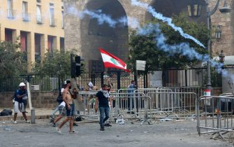 A Lebanese protester waves the national flag during clashes in downtown Beirut on October8, 2020, following a demonstration against a political leadership they blame for a monster explosion that killed more than 150 people and disfigured the capital Beirut. (Photo by Anwar AMRO / AFP) (Photo by ANWAR AMRO/AFP via Getty Images)