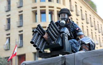 Lebanese security forces load tear gas into a launcher during clashes in downtown Beirut on October8, 2020, following a demonstration against a political leadership they blame for a monster explosion that killed more than 150 people and disfigured the capital Beirut. (Photo by Anwar AMRO / AFP) (Photo by ANWAR AMRO/AFP via Getty Images)