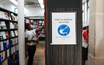 "A picture shows a sign reading ""Mask-wearing mandatory, thank you for your understanding"" as a customer wearing a face mask looks at books in a multimedia store on July 20, 2020, in Paris, on the first day of compulsory mask-wearing in enclosed public spaces in France in a bid to prevent a second wave of COVID-19 (novel coronavirus) infections. - As officials noted signs of an uptick in virus circulation, people in France will risk a fine of 135 euros (154 USD) starting on July 20 for failure to comply with a new decree to wear a mask in public places indoors, the government announced. (Photo by ALAIN JOCARD / AFP) (Photo by ALAIN JOCARD/AFP via Getty Images)"