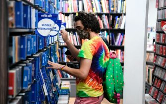 A customer wearing a face mask looks at CDs  in a multimedia store on July 20, 2020, in Paris, on the first day of compulsory mask-wearing in enclosed public spaces in France in a bid to prevent a second wave of COVID-19 (novel coronavirus) infections. - As officials noted signs of an uptick in virus circulation, people in France will risk a fine of 135 euros (154 USD) starting on July 20 for failure to comply with a new decree to wear a mask in public places indoors, the government announced. (Photo by ALAIN JOCARD / AFP) (Photo by ALAIN JOCARD/AFP via Getty Images)