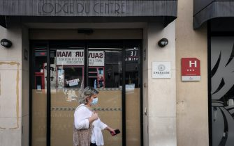 A woman wearing a protective mask passes by  a closed hotel on August 6, 2020 in Paris, amid the crisis linked with the Covid-19 pandemic caused by the novel coronavirus. (Photo by ALAIN JOCARD / AFP) (Photo by ALAIN JOCARD/AFP via Getty Images)
