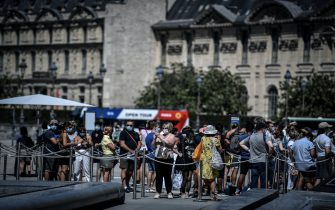 People wearing a protective face mask queue for the Louvre museum, in Paris on August 6, 2020. (Photo by STEPHANE DE SAKUTIN / AFP) (Photo by STEPHANE DE SAKUTIN/AFP via Getty Images)