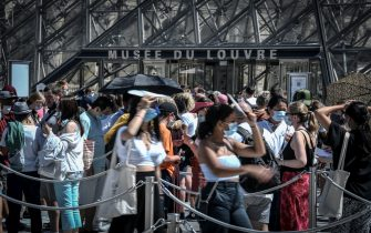 People wearing a protective face mask queue at the entrance of the Louvre Pyramid (Pyramide du Louvre) designed by Ieoh Ming Pei, at the Cour Napoleon, in Paris on August 6, 2020. (Photo by STEPHANE DE SAKUTIN / AFP) / RESTRICTED TO EDITORIAL USE - MANDATORY MENTION OF THE ARTIST UPON PUBLICATION - TO ILLUSTRATE THE EVENT AS SPECIFIED IN THE CAPTION (Photo by STEPHANE DE SAKUTIN/AFP via Getty Images)