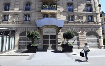 A woman wearing a protective mask passes in front of Hotel Barriere Le Fouquet's luxury hotel, closed due to the ongoing coronavirus crisis (COVID-19), on August 6, 2020 in Paris. (Photo by ALAIN JOCARD / AFP) (Photo by ALAIN JOCARD/AFP via Getty Images)