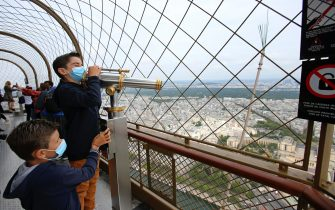 PARIS, FRANCE - July 15: A child wearing a protective face mask looks through a telescope on the day of the reopening of the top floor of the Eiffel Tower on July 15, 2020 in Paris, France. After nearly three months of closure due to the coronavirus pandemic (COVID-19), the Eiffel Tower today opens its 3rd floor to the public. (Photo by Chesnot / Getty Images)