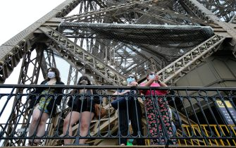 PARIS, FRANCE - July 15: Visitors wearing protective face masks look at the Paris city on the day of the reopening of the top floor of the Eiffel Tower on July 15, 2020 in Paris, France. After nearly three months of closure due to the coronavirus pandemic (COVID-19), the Eiffel Tower today opens its 3rd floor to the public. (Photo by Chesnot / Getty Images)