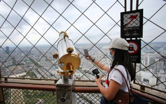 PARIS, FRANCE - July 15: A visitor wearing a protective face mask takes a picture of the Paris city on the day of the reopening of the top floor of the Eiffel Tower on July 15, 2020 in Paris, France. After nearly three months of closure due to the coronavirus pandemic (COVID-19), the Eiffel Tower today opens its 3rd floor to the public. (Photo by Chesnot / Getty Images)