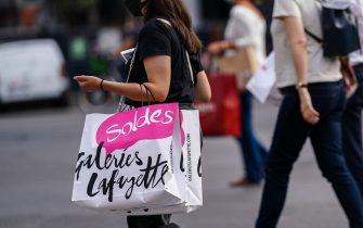 "PARIS, FRANCE - JULY 23: A passerby wears a black face mask, a black t-shirt, holds a ""Galeries Lafayette Soldes"" paper shopping bag, on July 23, 2020 in Paris, France. (Photo by Edward Berthelot/Getty Images)"