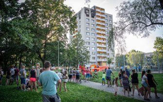 TOPSHOT - People look on as firefighters work at the scene where a fire broke out in an apartment block in Bohumin, eastern Czech Republic on August 8, 2020, killing eleven people including three children. - Police originally reported ten dead in the fire in a 13-storey concrete block of flats in the city of Bohumin on the Czech-Polish border some 300 kilometres (190 miles) east of the capital Prague. (Photo by Lukas Kabon / AFP) (Photo by LUKAS KABON/AFP via Getty Images)