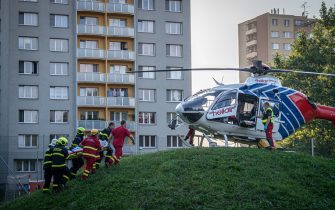 Firefighters carry a stretcher to a waiting helicopter at the scene where a fire broke out in an apartment block in Bohumin, eastern Czech Republic on August 8, 2020, killing eleven people including three children. - Police originally reported ten dead in the fire in a 13-storey concrete block of flats in the city of Bohumin on the Czech-Polish border some 300 kilometres (190 miles) east of the capital Prague. (Photo by Lukas Kabon / AFP) (Photo by LUKAS KABON/AFP via Getty Images)
