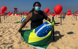 RIO DE JANEIRO, BRAZIL - AUGUST 08: A demonstrator from the NGO 'Rio De Paz' ties a Brazilian flag to a cross in Copacabana beach on August 8, 2020 in Rio de Janeiro, Brazil. The demonstration is a tribute in memory of the almost 100 thousand Brazilians killed by the coronavirus (COVID-19). In Rio de Janeiro alone, more than 14,000 deaths were confirmed. (Photo by Alessandra del Bene/Getty Images)