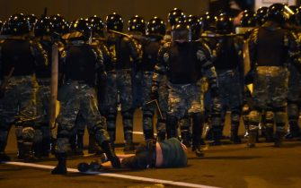 TOPSHOT - A man lies on the ground in front of riot police during a protest after polls closed in Belarus' presidential election, in Minsk on August 9, 2020. (Photo by Sergei GAPON / AFP) (Photo by SERGEI GAPON/AFP via Getty Images)
