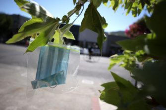 SAN ANSELMO, CALIFORNIA - AUGUST 10: A surgical mask in a Ziploc bag hangs from a tree at Creek Park on August 10, 2020 in San Anselmo, California. The group Age-Friendly Marin Network has started to hang clean face masks from trees in San Anselmo's Creek Park that are free to those who do not have a mask and to encourage people to wear masks to help control COVID-19.  (Photo by Justin Sullivan/Getty Images)
