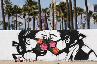VENICE, CALIFORNIA - MARCH 21: Palm trees stand behind a street art piece by artist Pony Wave depicting two people kissing while wearing face masks on Venice Beach on March 21, 2020 in Venice, California. California Governor Gavin Newsom issued a â  stay at homeâ   order for Californiaâ  s 40 million residents in order to slow the spread of coronavirus (COVID-19). Californians may still go to the beach without violating Newsomâ  s order as long as they maintain social distancing and adhere to other public health measures related to the coronavirus. (Photo by Mario Tama/Getty Images)