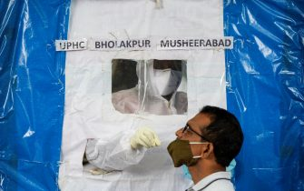 TOPSHOT - A health worker collects a swab from a resident at a makeshift free COVID-19 coronavirus testing booth in Hyderabad on August 10, 2020. (Photo by Noah SEELAM / AFP) (Photo by NOAH SEELAM/AFP via Getty Images)