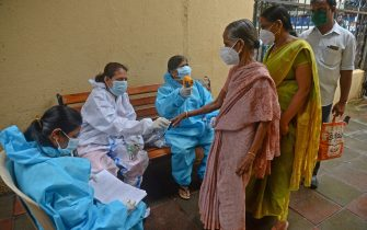 TOPSHOT - Health workers wearing protective gear use fingertip pulse oximeter and check the body temperature of residents during a COVID-19 coronavirus screening at Dharavi slums in Mumbai on August 18, 2020. - India's official coronavirus death soared past 50,000 on August 17 as the pandemic rages through smaller cities and rural areas where health care is feeble and stigmatisation rife. (Photo by INDRANIL MUKHERJEE / AFP) (Photo by INDRANIL MUKHERJEE/AFP via Getty Images)