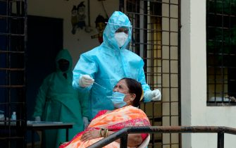 A health worker wearing personal protective equipment (PPE) collects a swab sample from a resident at a free COVID-19 coronavirus testing centre in Hyderabad, on August 18, 2020. - India's official coronavirus death toll soared past 50,000 on August 17 as the pandemic rages through smaller cities and rural areas where health care is feeble and stigmatisation rife. (Photo by NOAH SEELAM / AFP) (Photo by NOAH SEELAM/AFP via Getty Images)