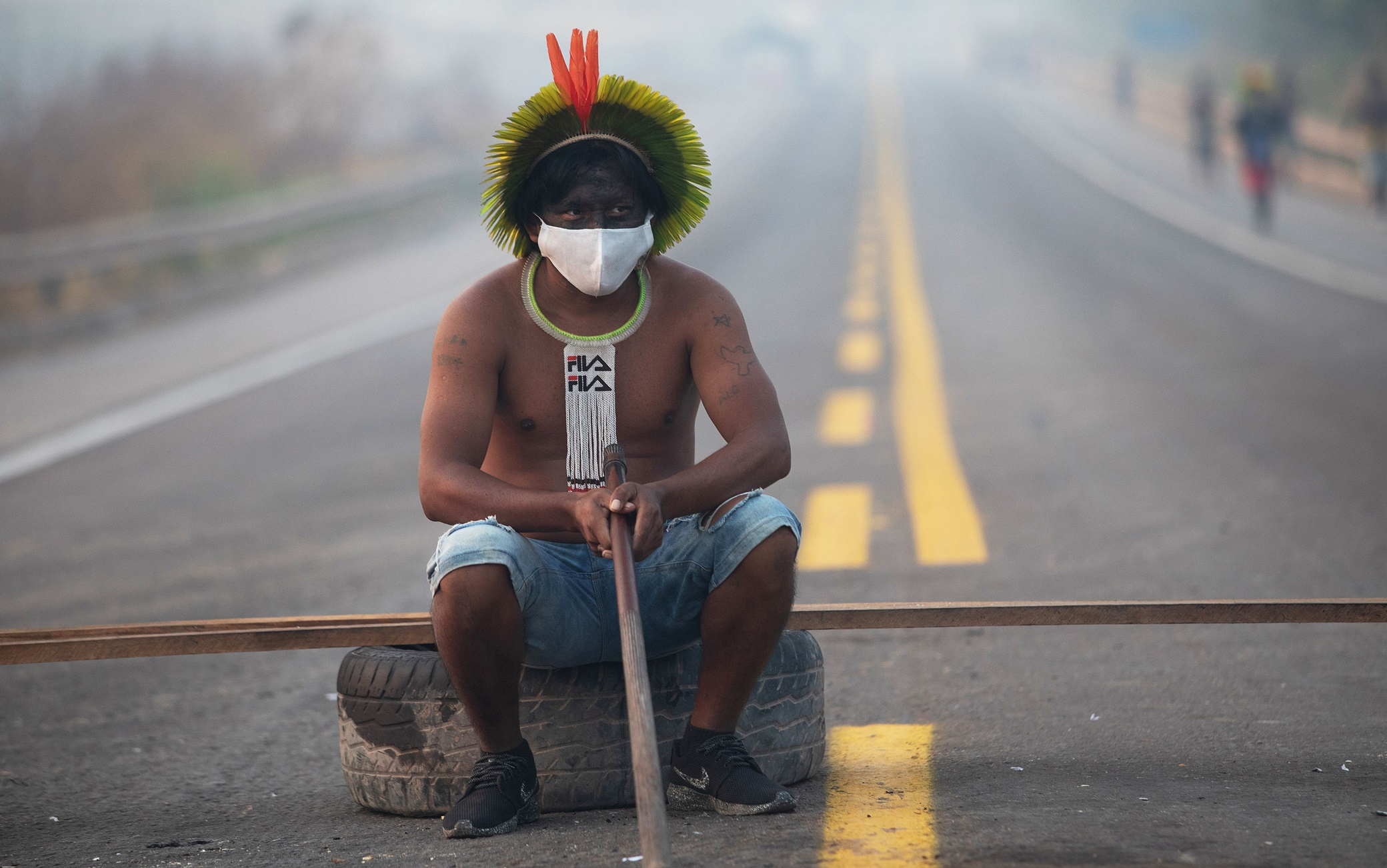 TOPSHOT - A member of the Kayapo tribe sits after they blocked highway BR163 during a protest on the outskirts of Novo Progresso in Para State, Brazil, on August 18, 2020 amid the COVID-19 novel coronavirus pandemic. - Brandishing bows and arrows, dozens of indigenous protesters blocked a main highway through the Brazilian Amazon, demanding help against the new coronavirus and an end to illegal mining and deforestation. (Photo by JOÃ O LAET / AFP) (Photo by JOAO LAET/AFP via Getty Images)
