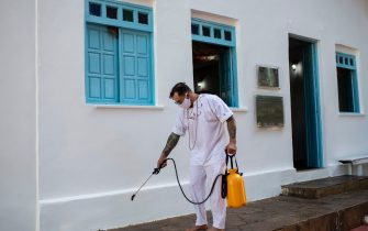 SALVADOR, BRAZIL - AUGUST 17: Francisco Rizzuto, 42, 'Filho de Santo', sanitizes the Templo de Candomblé Casa de à sùmàrè amidst the coronavirus (COVID-19) pandemic on August 17, 2020 in Salvador, Brazil. The 'Casa de à sùmàrè' is one of the oldest and most traditional Candomblé Terreiros in Bahia and dates back to the time of the formation of the religion in Brazil. Its origin dates from the beginning of the 19th century and was marked by the struggle and resistance of enslaved Africans who, forced to abandon their lands and family ties in Africa, did not renounce their culture and faith. (Photo by Bruna Prado/Getty Images)