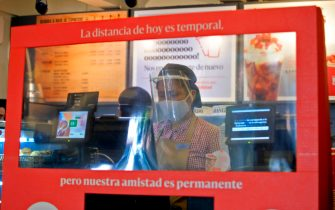 An employee is seen behind a screen reading Today's distance is temporary. Our friendship is permanent at the counter of a coffee shop preparing to reopen in Bogota on August 14, 2020, amid the new coronavirus pandemic. - Bogota's Mayor Claudia Lopez authorized some passenger flights at El Dorado International Airport and will allow restaurants with outdoor seating to reopen from September 1. (Photo by DANIEL MUNOZ / AFP) (Photo by DANIEL MUNOZ/AFP via Getty Images)
