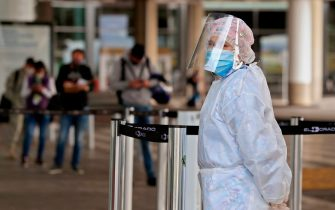 A woman wearing personal protective equipment waits for passengers at the entrance of El Dorado International Airport in Bogota on August 14, 2020, amid the new coronavirus pandemic. - Bogota's Mayor Claudia Lopez authorized some passenger flights at El Dorado International Airport and will allow restaurants with outdoor seating to reopen from September 1. (Photo by DANIEL MUNOZ / AFP) (Photo by DANIEL MUNOZ/AFP via Getty Images)