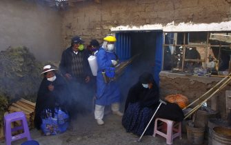 TOPSHOT - A funerary employee in protective gear disinfects the home of a COVID-19 victim as relatives mourn outside, before taking the casket to the local cemetery for burial in the remote Aymara highland village of Acora, one hour away from the city of Puno, close to the border with Bolivia on August 9, 2020. - Peru registered a new daily record of deaths from the novel coronavirus on August 9, with 228 deaths, surpassing 21,000, amid a vigorous rebound of infections five weeks after the end of a long national confinement. The country, with 33 million inhabitants, is the third country in Latin America in deaths and infections, behind Brazil and Mexico. (Photo by Carlos MAMANI / AFP) (Photo by CARLOS MAMANI/AFP via Getty Images)