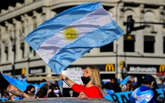 People wave Argentine flags during a protest against the government health policies, regarding the tight lockdown measures against the spread of the novel COVID-19 coronavirus, at 9 de Julio avenue, in Buenos Aires, Argentina, on August 17, 2020. (Photo by RONALDO SCHEMIDT / AFP) (Photo by RONALDO SCHEMIDT/AFP via Getty Images)