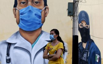 "A women walks in front of a mural, painted by workers of the Zapopan city hall as part of the program ""Zapopart"", as a tribute to essential workers who have cared for citizens during the COVID-19 pandemic in Zapopan, state of Jalisco, Mexico, on August 12, 2020, amid the novel coronavirus pandemic. (Photo by ULISES RUIZ / AFP) (Photo by ULISES RUIZ/AFP via Getty Images)"