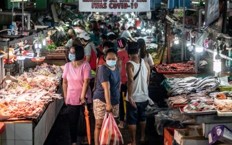 People wearing masks shop for fresh food at a market in Manila on August 6, 2020. - The Philippines plunged into recession after its biggest quarterly contraction in four decades, data showed on August 6, as the economy reels from COVID-19 coronavirus lockdowns that have wrecked businesses and thrown millions out of work. (Photo by Lisa Marie David / AFP) (Photo by LISA MARIE DAVID/AFP via Getty Images)