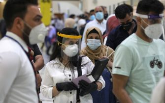 Passengers wearing protective masks wait for flights at the departure hall of Baghdad international airport following its reopening on July 23, 2020, after a closure forced by the coronavirus pandemic restrictions aimed at preventing the spread of the deadly COVID-19 illness in Iraq. (Photo by AHMAD AL-RUBAYE / AFP) (Photo by AHMAD AL-RUBAYE/AFP via Getty Images)