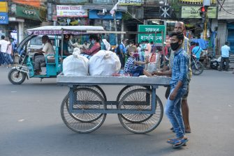 A man and his son push a cart where a young boy sits in Siliguri on August 19, 2020, as a state-imposed lockdown will be held on August 20 and 21 against the surge in COVID-19 coronavirus cases. (Photo by DIPTENDU DUTTA / AFP) (Photo by DIPTENDU DUTTA/AFP via Getty Images)