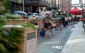 NEW YORK, NEW YORK - AUGUST 19: A man wearing a mask sits at  recently opened outdoor tables outside of Chelsea Market as the city continues Phase 4 of re-opening following restrictions imposed to slow the spread of coronavirus on August 19, 2020 in New York City. The fourth phase allows outdoor arts and entertainment, sporting events without fans and media production. (Photo by Alexi Rosenfeld/Getty Images)
