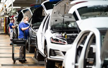 Employees of German car maker Volkswagen (VW) work at the assembly line of the company's plant in Wolfsburg, northern Germany, after production at the plant restarted on April 27, 2020, amid the new coronavirus COVID-19 pandemic. (Photo by Swen Pförtner / POOL / AFP) (Photo by SWEN PFORTNER/POOL/AFP via Getty Images)