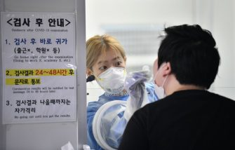 A medical staff in a booth takes test samples for the COVID-19 coronavirus from a visitor at a coronavirus testing station in Seoul on August 18, 2020. - South Korea on August 18 ordered nightclubs, museums and buffet restaurants closed and banned large-scale gatherings in and around the capital as a burst of new coronavirus cases sparked fears of a major second wave. (Photo by Jung Yeon-je / AFP) (Photo by JUNG YEON-JE/AFP via Getty Images)