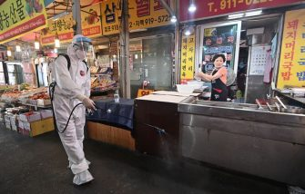 A health official wearing protective gear sprays disinfectant at a market near the Sarang Jeil Church, a new coronavirus infection cluster, in Seoul on August 18, 2020. - South Korea on August 18 ordered nightclubs, museums and buffet restaurants closed and banned large-scale gatherings in and around the capital as a burst of new coronavirus cases sparked fears of a major second wave. (Photo by Jung Yeon-je / AFP) (Photo by JUNG YEON-JE/AFP via Getty Images)