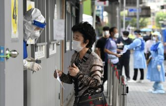 A health official (L) wearing protective gear guides a visitor at a COVID-19 coronavirus testing station in Seoul on August 18, 2020. - South Korea on August 18 ordered nightclubs, museums and buffet restaurants closed and banned large-scale gatherings in and around the capital as a burst of new coronavirus cases sparked fears of a major second wave. (Photo by Jung Yeon-je / AFP) (Photo by JUNG YEON-JE/AFP via Getty Images)